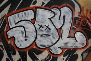 letter spray painted in white red graffiti on wall